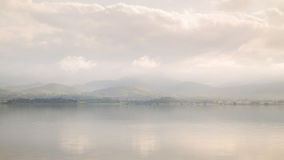 Misty morning of lake and mountain range Stock Images