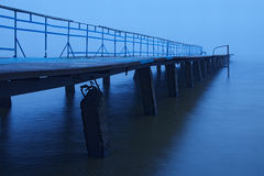 Misty morning on the lake. Old abandoned pier goes into the fog Stock Photos