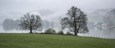 Misty morning landscape over Lake Windermere in Lake District in Royalty Free Stock Images