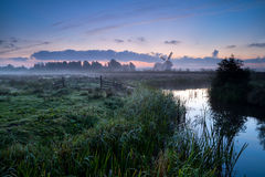 Misty morning over Dutch farmland with windmill and river Stock Image