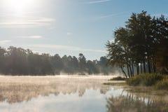 Misty Morning Reflections auf ruhigem See lizenzfreie stockbilder