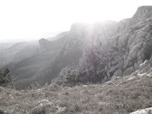 Misty morning in a rocky mountain gorge sunlit panoramic view from above. Misty morning in a rocky mountain gorge sunlit panoramic view from a above royalty free stock image