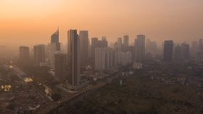 Misty morning with skyscrapers in Jakarta. JAKARTA, Indonesia - October 26, 2018: Beautiful aerial view of misty morning with silhouette of skyscrapers near the royalty free stock image