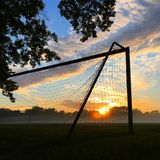 Misty morning. The sun rises on a suburban soccer field, highlighting the mist that developed overnight Royalty Free Stock Photography