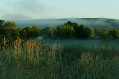 A Misty Morning Sunrise Over a Picturesque Landscape. Foggy Meadow at Sunrise. A Misty Morning Sunrise Over a Picturesque Landscape. An Early Morning Over a Royalty Free Stock Images