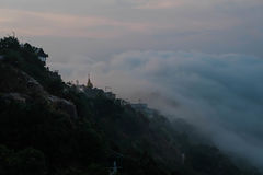 Misty morning at top of mountain. Top of mountain cover with fog but pagoda still visible at Myanmar Stock Photos