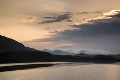 Misty mountain landscape at sunrise reflected in lake Stock Images