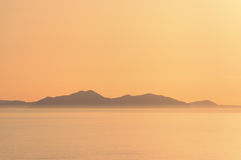Misty mountain over sea with orange color Royalty Free Stock Photography