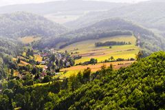 Misty mountain valley with fields and meadows. Scenic picturesque farmland landscape. Vast aerial view of Nowa Wies Klodzka village in the Owl Mountains Gory Royalty Free Stock Photography