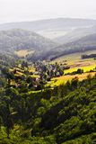 Misty mountain valley with fields and meadows. Scenic picturesque farmland landscape. Vast aerial view of Nowa Wies Klodzka village in the Owl Mountains Gory Royalty Free Stock Photo