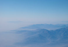 Misty mountains with blue skies Royalty Free Stock Image