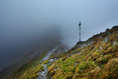 Misty mountains and hiking trail. Alpine landscape with hiking trail going on the mountain in the mist Stock Photography