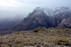 Misty mountaintop. A scenic landscape view of misty, snow covered mountains in the distance at Red Rock State Park, Nevada (USA Stock Photography