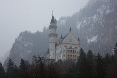 Misty Neuschwanstein Castle. View of the Neuschwanstein Castle in Alps mountain at misty winter time stock photography