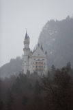 Misty Neuschwanstein Castle. View of the Neuschwanstein Castle in Alps mountain at misty winter time royalty free stock images