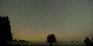 Misty Northern Lights Panorama. Powerful northern lights over night sky in Tahula Saaremaa Estonia. Aurora borealis was strong, but mist made it mysterious Royalty Free Stock Images
