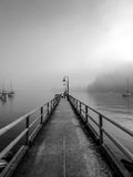 Misty Pier. A woman and her dog enjoying the early morning mist on the pier at Deep Cove, North Vancouver stock photos