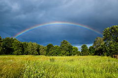 Misty Rainbow Arches Over Field and Trees Royalty Free Stock Photos