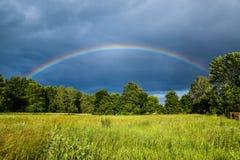 Misty Rainbow Arches Over Field und Bäume lizenzfreie stockfotos