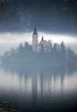 Misty Reflection. The Bled island church reflecting in the water in the misty afternoon Royalty Free Stock Image