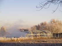 Misty river and greenhouse. Scenic view of misty river in countryside with large greenhouse in foreground Royalty Free Stock Photo