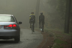 Misty road cyclists. Pair of cyclists on misty road about to be overtaken by car Royalty Free Stock Photos