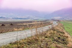 Misty road landscape. Misty autumn foggy morning to the mountains landscape Royalty Free Stock Photo