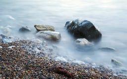 Misty Rocks. Rocks and seaweed on the shoreline Royalty Free Stock Image