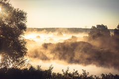 Misty rural landscape during golden hour at river bank in the early morning Royalty Free Stock Image