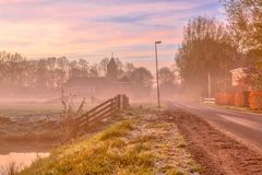 Misty street in dutch village. Misty street in dutch rural village on the countryside with church in colorful pink early morning light stock image