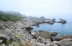 Misty summer stony coast landscape Royalty Free Stock Image