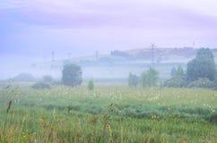 Misty Summer Sunrise nelle montagne: Erba alta, nebbia spessa, alberi, linea elettrica torri e nuvole porpora drammatiche Energia immagini stock libere da diritti