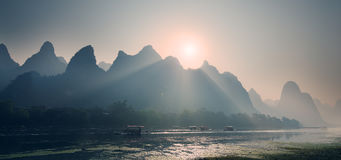 Misty sunrise behind strange mountain Stock Image