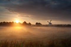 Misty sunrise and Dutch windmill Stock Photography
