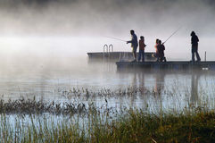 Misty sunrise fishing on lake Royalty Free Stock Photos