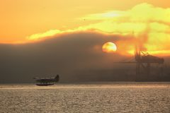 Misty Sunrise Floatplane Departure, Vancouver. A floatplane takes off over Burrard Inlet at sunrise. Vancouver, British Columbia, Canada Royalty Free Stock Photos