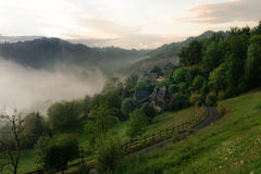 Misty sunrise on forest hill village. Beautiful forest hill landscape on a misty dawn morning, with green meadows, some picturesque old houses, trees and a windy royalty free stock photo