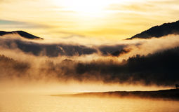 Misty Sunrise by a mountain lake Royalty Free Stock Image
