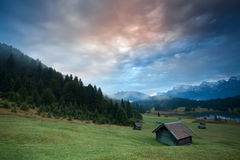 Misty sunrise over huts by Geroldsee lake Stock Photos