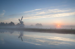 Misty sunrise over river and windmill Royalty Free Stock Images