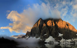 Misty sunrise shadows on floe mountain above the lake Royalty Free Stock Photography