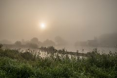Misty sunrise at the waterfront stock photography