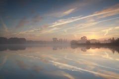 Misty sunrise on wild lake Stock Image