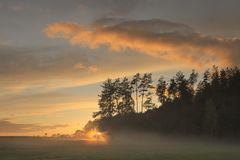 A misty sunset with a view of a field and forest Stock Image