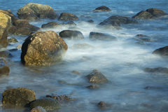 Misty surf among boulders, Hammonasset Beach, Madison, Connectic Royalty Free Stock Photos