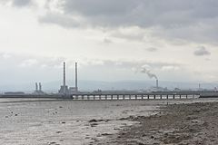 Misty view from across the water on Poolberg peninsula, with the chimneys of the power generation station , view from the beach. Misty view from across the water royalty free stock image