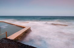 Misty water tidal pool. Misty water flowing at sunset by a coastal tidal pool royalty free stock photos