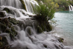 Misty waterfalls flowing into lake Stock Photography