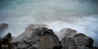 Misty Wave Hits Rocky Shore. Taken at slow shutter speed Royalty Free Stock Photos