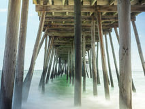 Misty Waves under Wooden Pier. Timed exposure of waves under wooden pier Stock Photo
